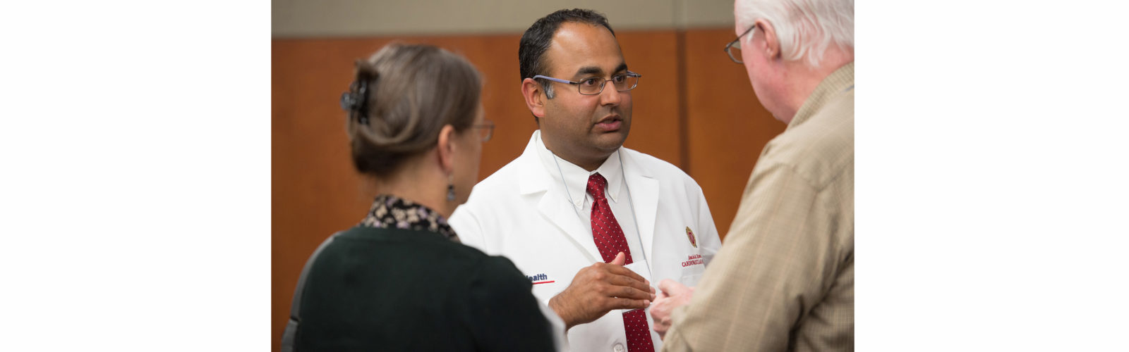 Dr. Amish Raval talking to a man and a woman at a lecture